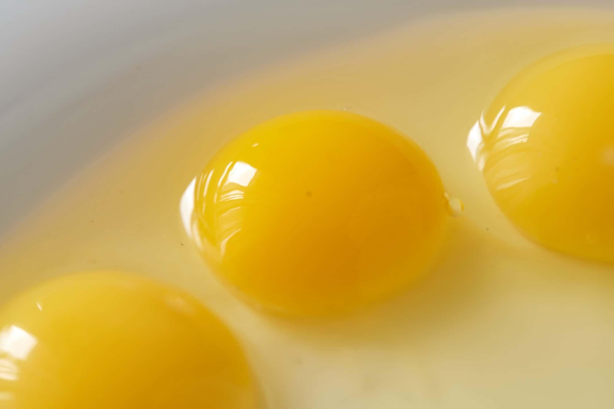 Three broken quail eggs in white plate on black background