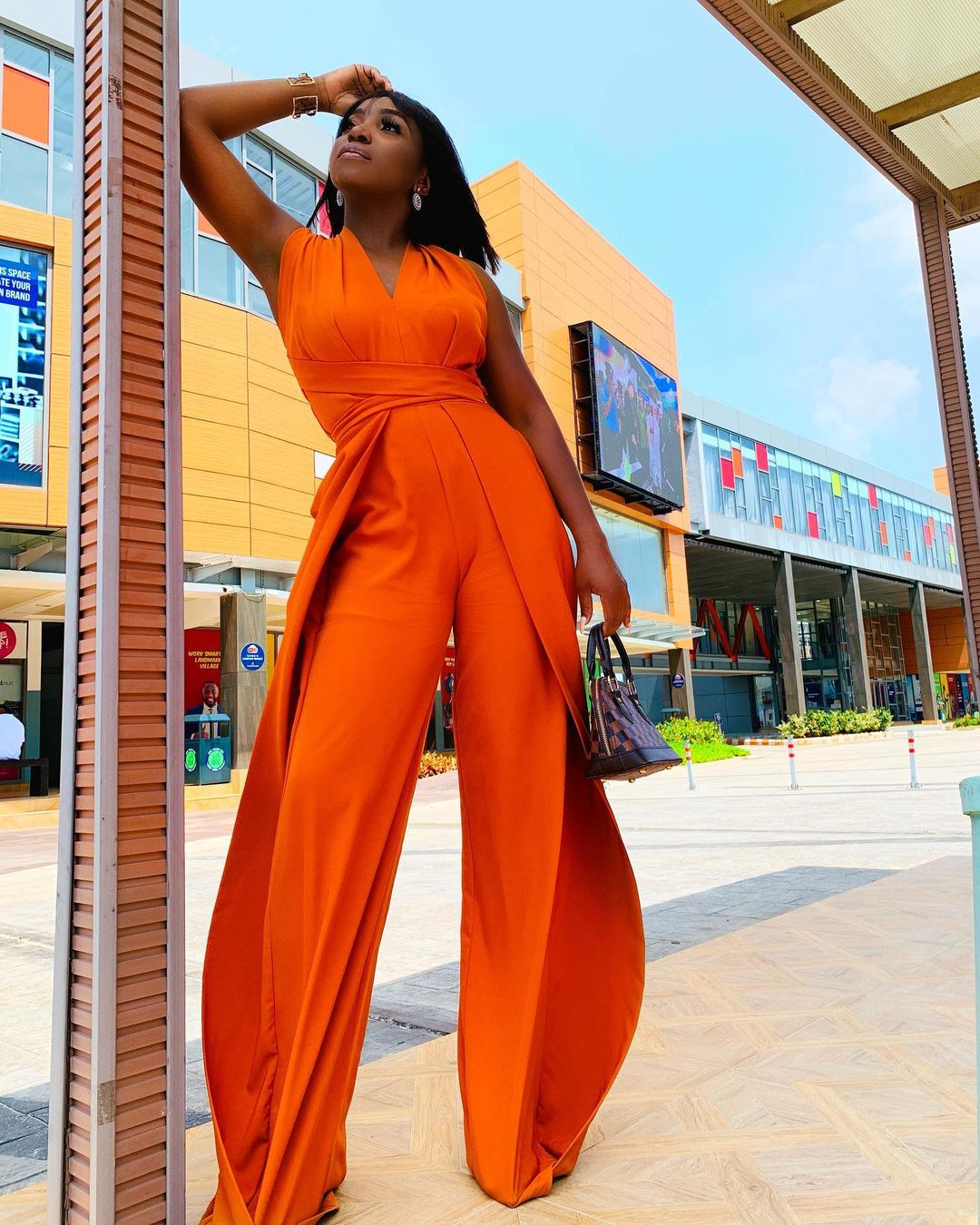 A Queen Rocking An Orange Classy Jumpsuit